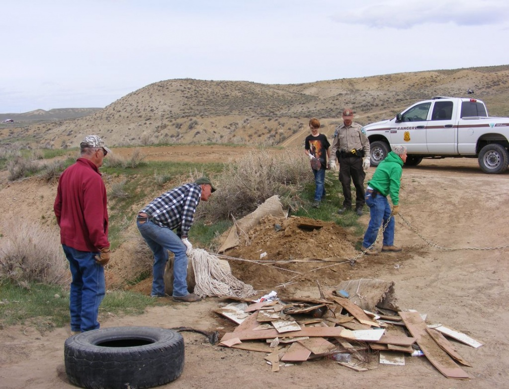 A photo from the Government Draw Clean-up in 2014 (From left to right): Dan Merrill, Stan Rinker, Xander Davidson, BLM Law Enforcement Ranger Thomas Howell and Chuck Johnson clean up an illegal dump of old carpet and construction material. (Fremont  County ATV Photo)