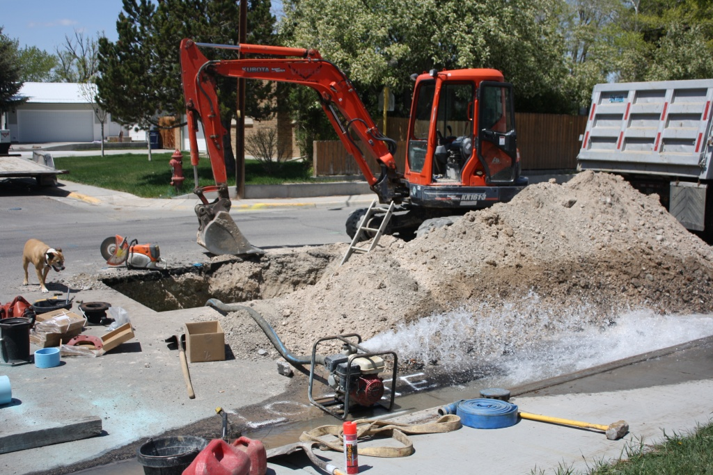 A pump disgorged water from the working space where two men were replacing a defective valve on a city water line along North 8th West on Saturday. (Ernie Over photo)
