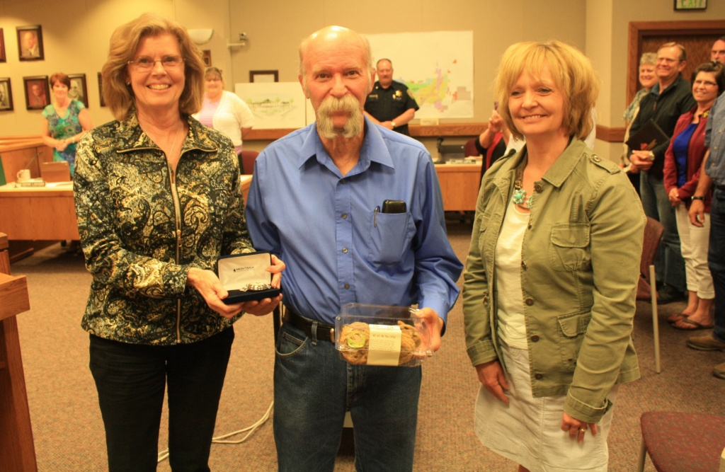 Community Development Director Sandy Luers, left, presented Clyde Anderson with a silver pocket watch while permit tech Kristi Petersen gave him a box of cookies on his retirement from the department after 12 years of service to the city. (Ernie Over photo)
