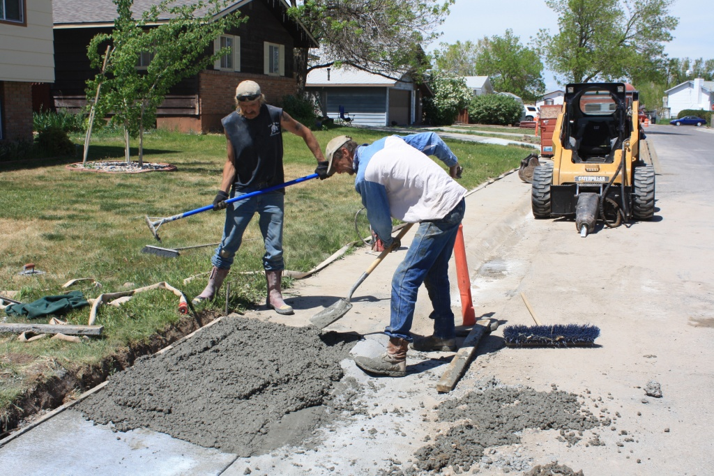 Scott Hunt, left, and Eric Inberg from ERI Engineering work on replacing a section of sidewalk on North 12th East.  (eo)