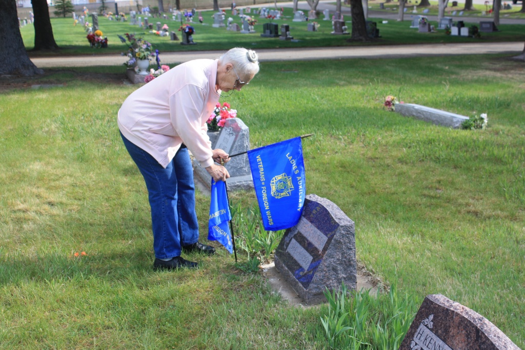 Cerela Overgard places a VFW Auxiliary Flag at Mountain View Cemetery Saturday morning. (eo)