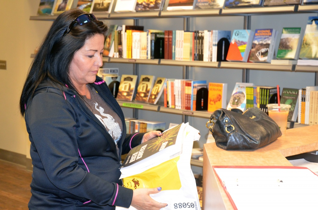 Avis Garcia picks up a book in the University Store for a summer course in the UW College of Education's doctoral program in counselor education and supervision. (UW Photo)