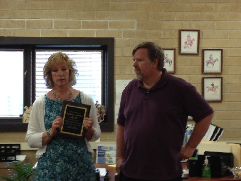 Fremont County Clerk Julie Freese presents Mike Stalder with a plaque.