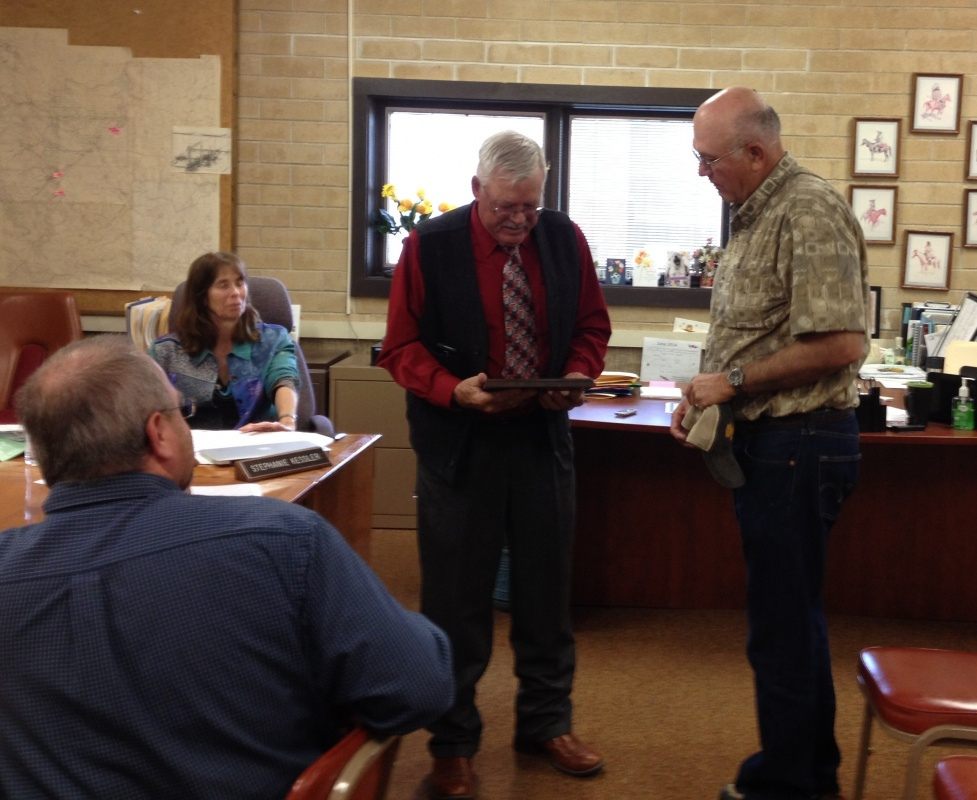 Fremont County Commission Chairman Doug Thompson presents Leonard Hinkle, right, with a plaque.
