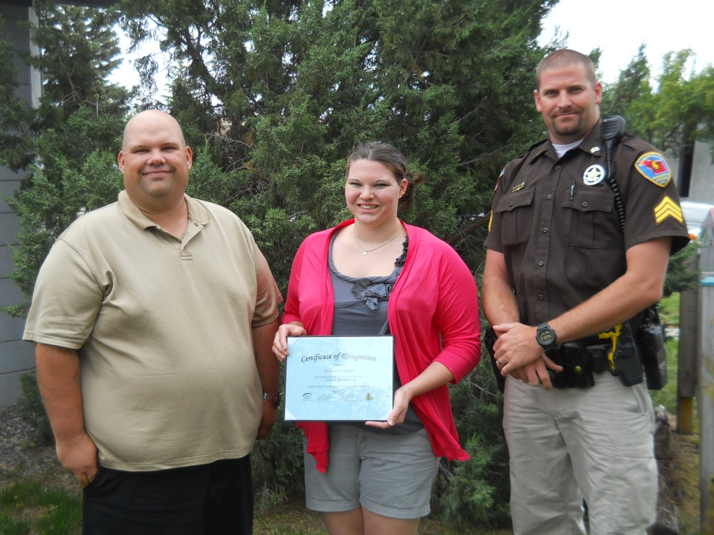 Riverton Seat-Belt Survivor Alexandra Baxter, Tom Cunningham (left) of Injury Prevention Resources and Fremont County Sheriff's Deputy Michael Hutchison during Tuesday's seat-belt survivor award presentation. (WYDOT)