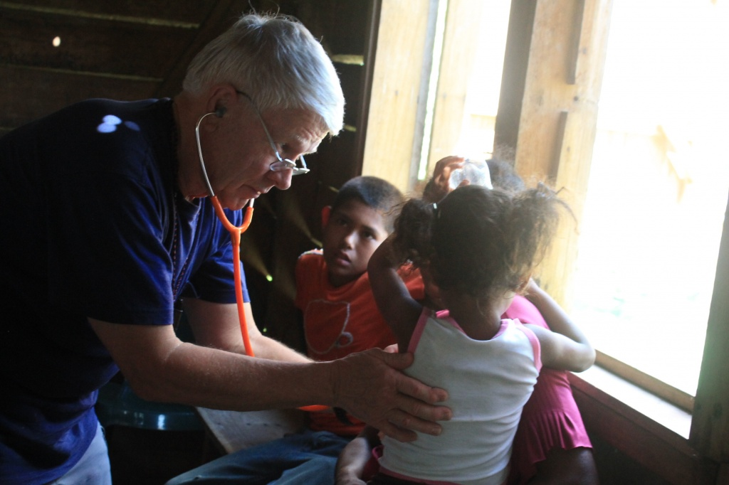 Dr. Hart Jacobsen at work on a young patient during this year's Mission of Mercy: Honduras.
