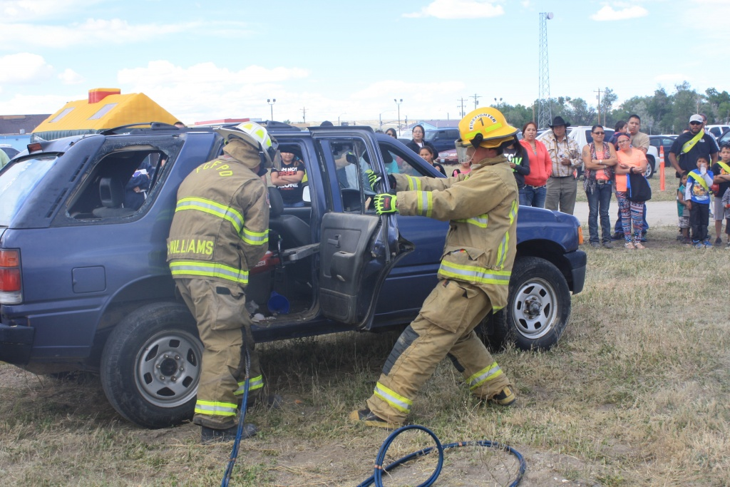 Fort Washakie Firefighters are pictured cutting a door off of a vehicle during a Jaws of Life Demonstration at the Wind River Summer Safety Fair at Ethete on Wednesday.  (eo)