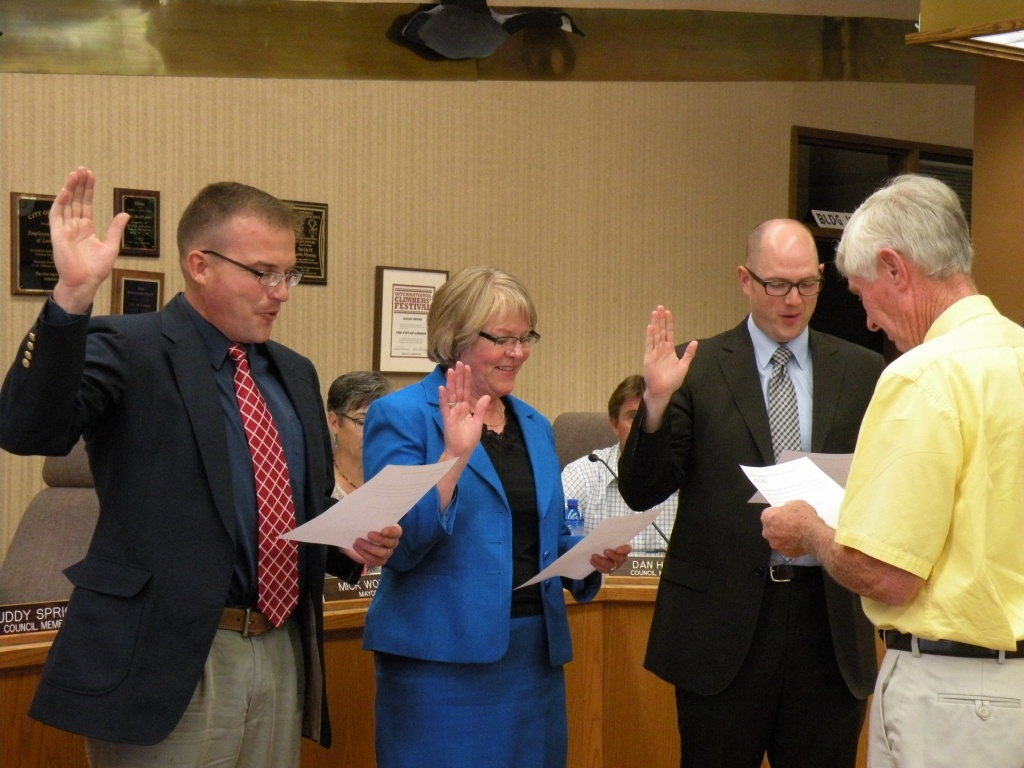 From left, James Whiting, Wendy Merrill and Adam Phillips are sworn into office by Mayor Mick Wolfe.