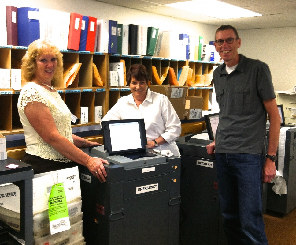 Julie Freese (County Clerk) , Darlene Vaughan (FC Republican Chair) and Bruce Palmer (FC Democrat Chair) testing the machines. Photo by Sara McWain.