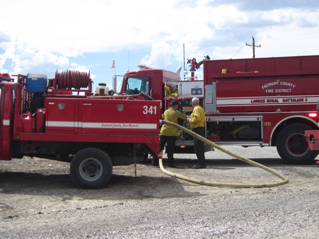 Fire District brush trucks are filled from a larger tanker. (file photo)