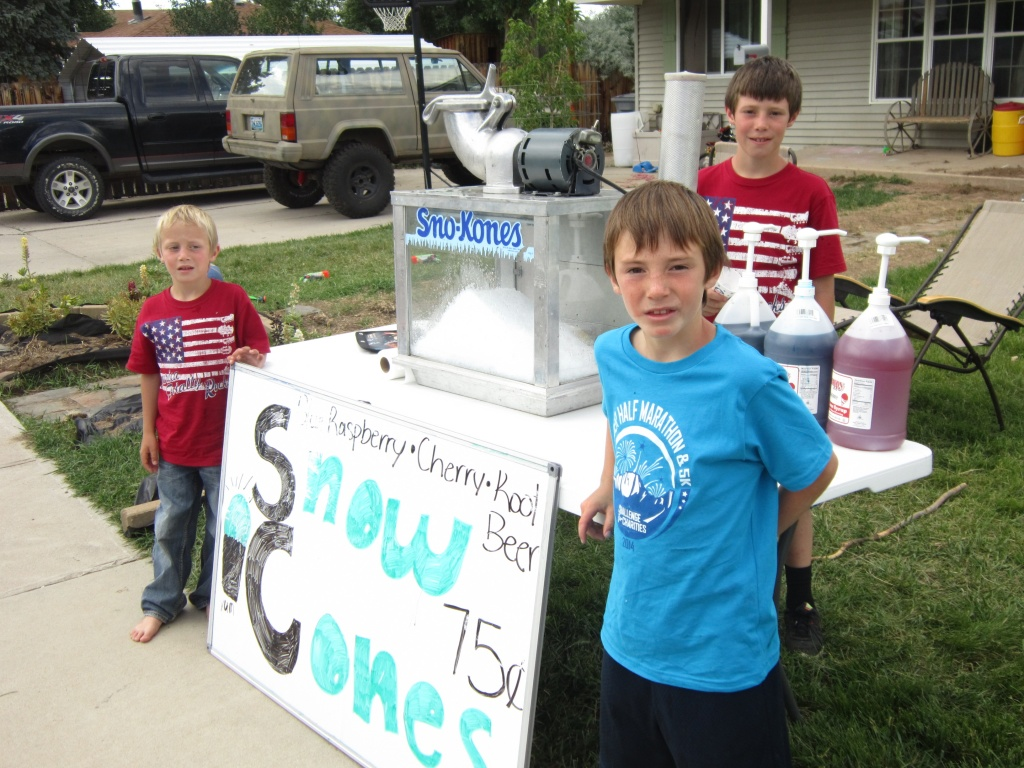 Mason, 7, Logan, 9, and Colton Wietzki, 11, whip up a pretty good snow cone at the stand in their front yard in the 500 block of Shoshone. (Ernie Over photo)