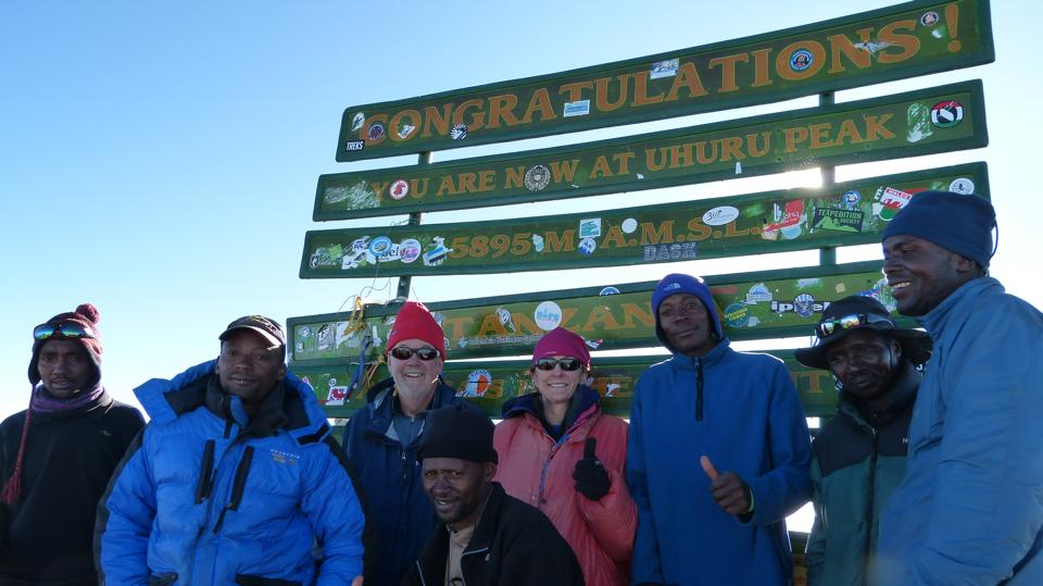 Lander's John Metcalf and Michelle Woodruff are surrounded by their guides at the peak of Mount Kilimanjaro in Tanzania.