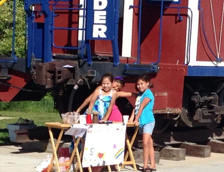 The girls set up their stand next to the caboose in Lander's Jaycee Park. Photo by Deana Aaragon.