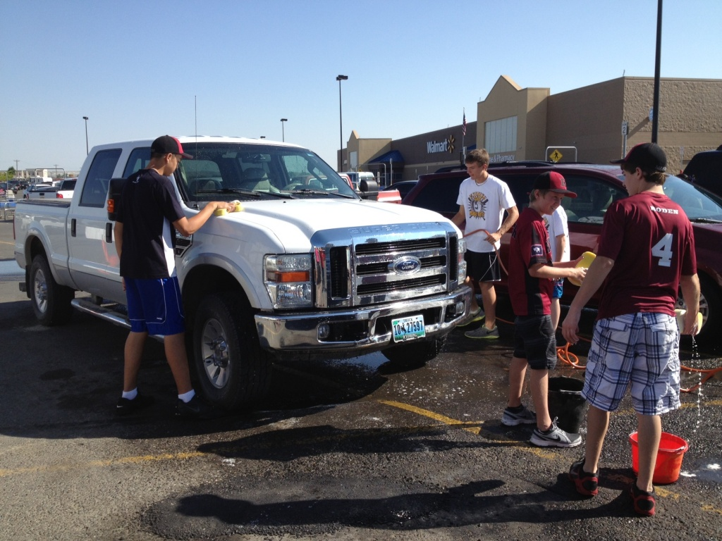 Team members wash and shine a big Ford at this morning's car wash. (Ernie Over photo)
