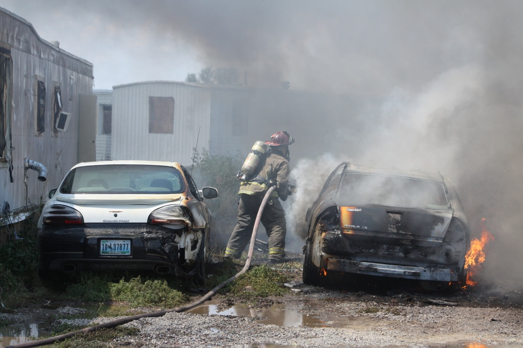 Firefighters worked to extinguish fire that spread into three vehicles parked next to the fire scene. (Chico Martinez, RFD photo)