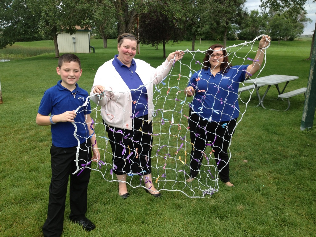 Aaron, 10, mom Chrystal and the Assistant to the Past President Brandi Lippert pose with Aaron's net. (Ernie Over photo)