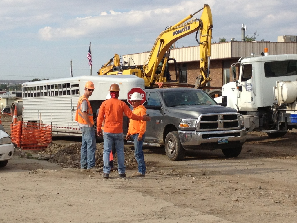 Construction workers at the site talked in a group after a female flagger was struck by the side mirror of a passing vehicle. (Ernie Over photo)