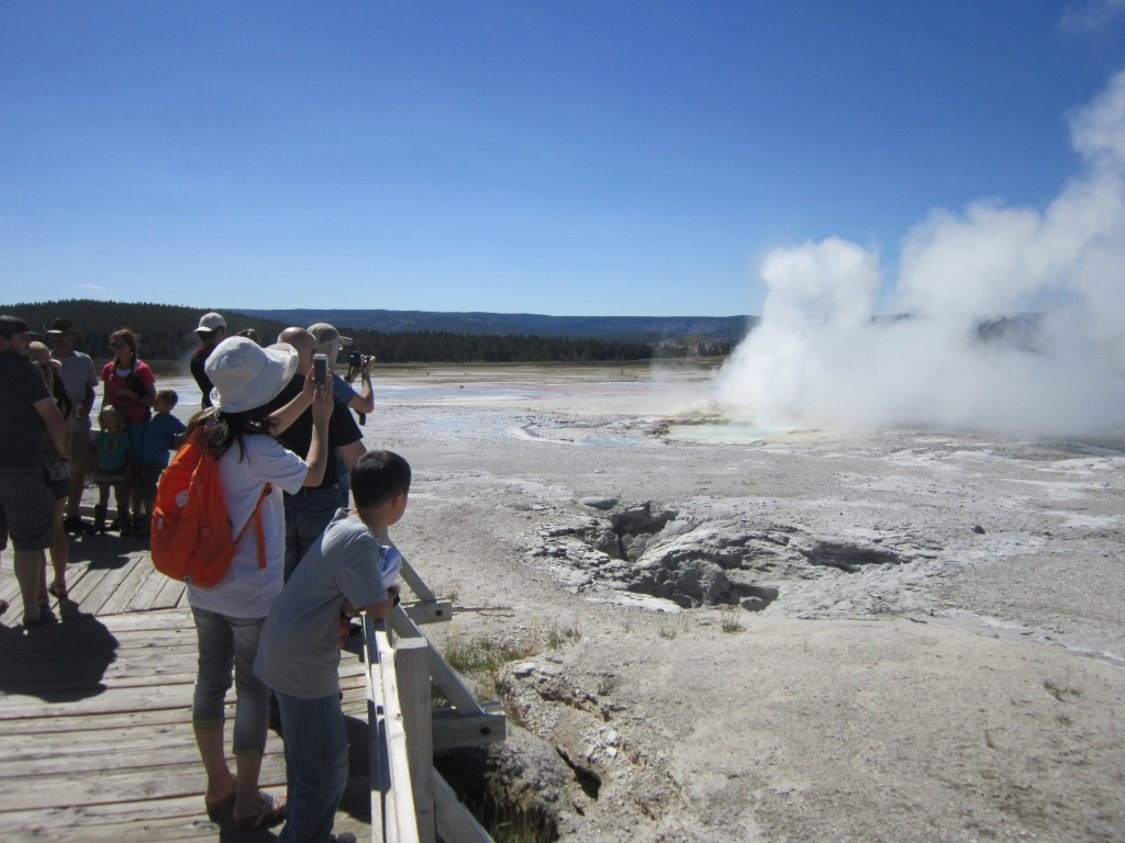 Tourists photograph the perpetual geyser eruption at the Fountain Paint Pots walk in Yellowstone National Park.