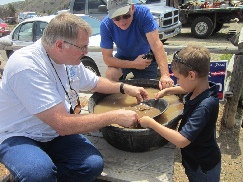 Cael Arbogast of Riverton got a gold panning demonstration from Randy Hutchison while Grandpa Greg from Michigan looked on. (Ernie Over photo)