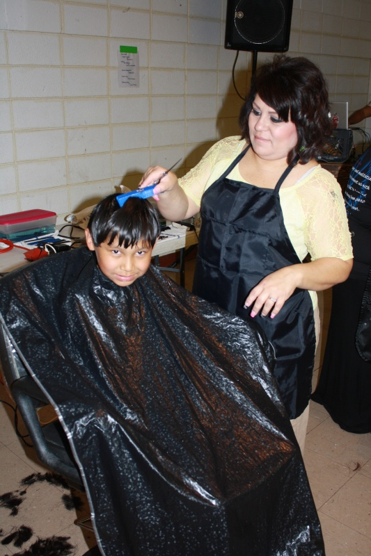 Tyree  Brown, 8, a third grader this year at Wyoming Indian Elementary School, received a trim from Renee Manzanares, a TERO volunteer. (Ernie Over photo)