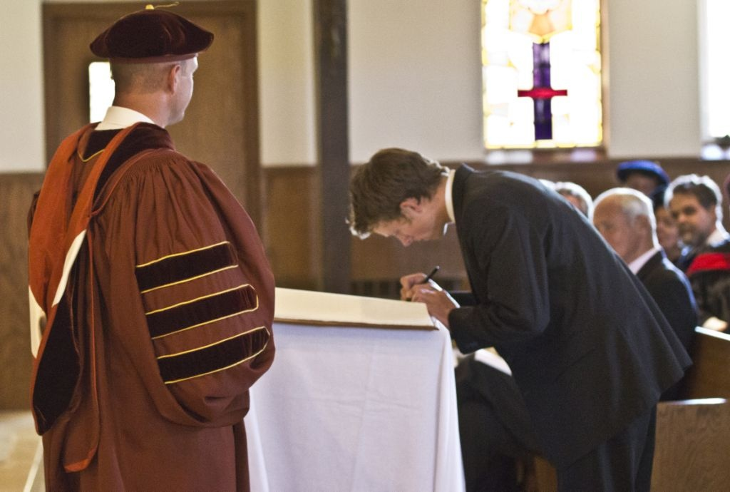 President Kevin Roberts looks as a student signs the Student Register at WCC's Convocation Mass and formal Matriculation  ceremony this past fall.