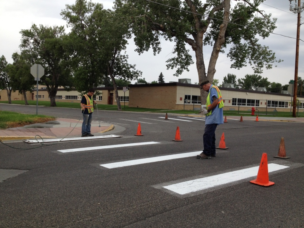 A city painting crew worked on repainting crosswalk markings near Ashgrove School on Monday. (Ernie Over photo)