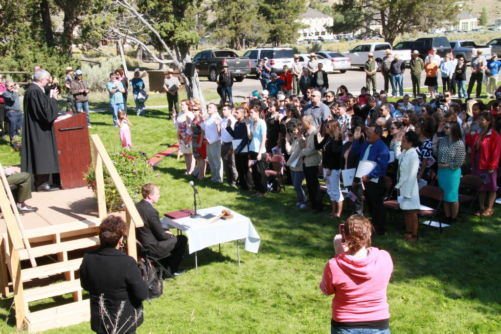 Judge Carman administering the Oath of Allegiance to 42 new citizens at an outdoor ceremony in Yellowstone National Park. NPS Photo by Bob Greenburg.