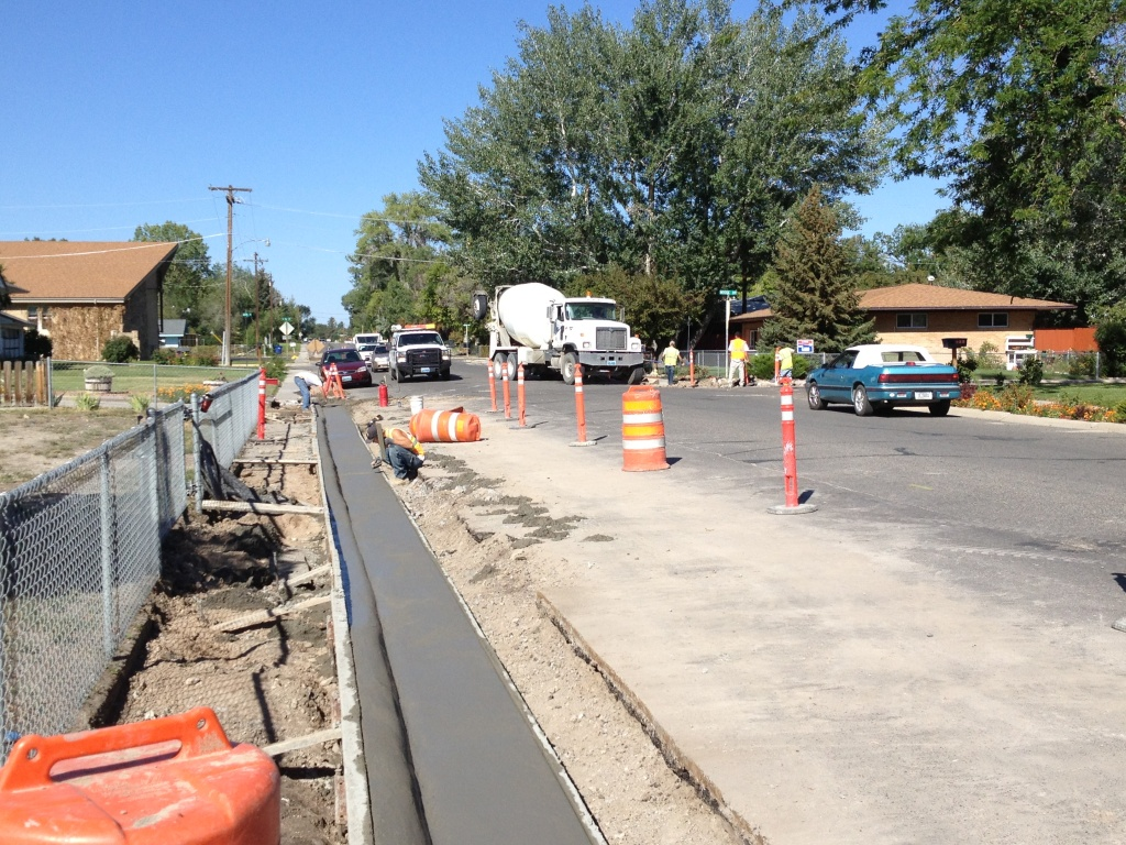 A new curb and gutter is being finished along East Sunset while concrete is poured for a sidewalk on the other side of the street. (Ernie Over photo)