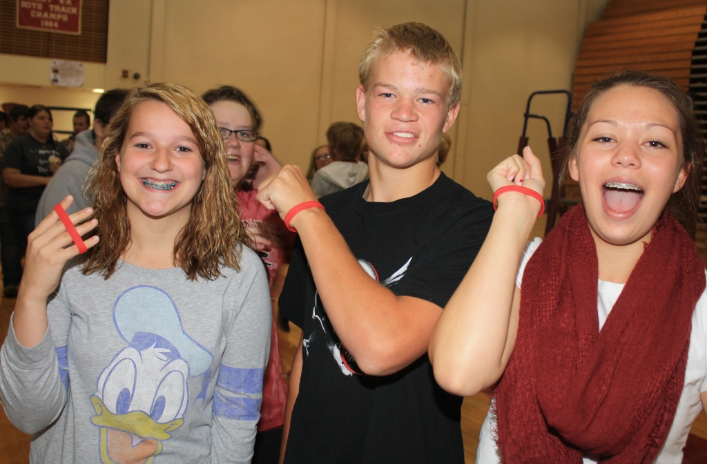 Sophomore Ali Valdez, Junior Brayden Draper and Sophomore Charlie Peterson signed the graduation pledge and showed off their red gel bracelets indicating their pledge. (Ernie Over photo)