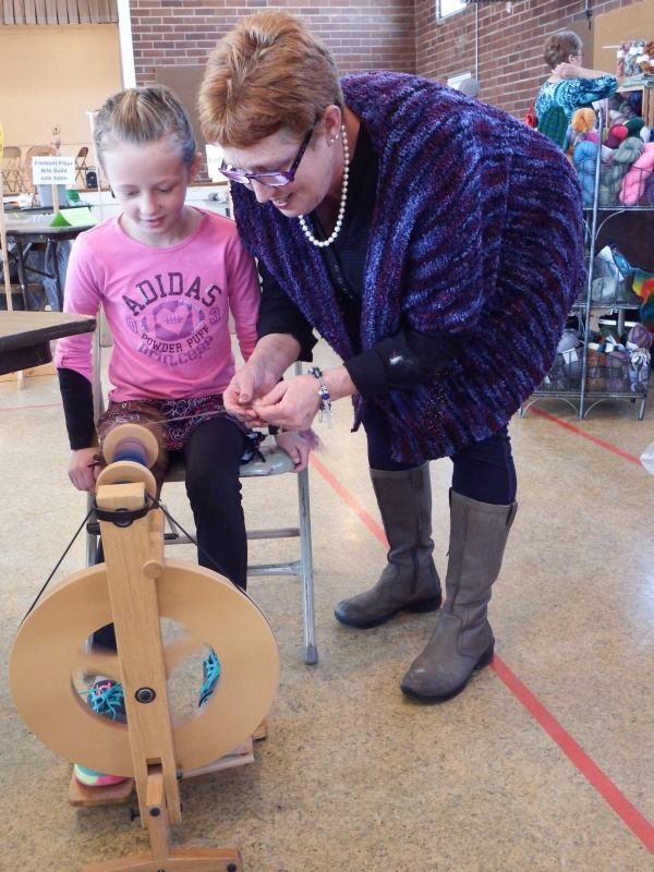 Madi Fossey, 8, received a lesson on a foot activated spinning wheel from Cinde Pfisterer. Spinning fiber into yarn requires coordination to keep the wheel from reversing direction and fouling the spool. (Photo by Ernie Over)