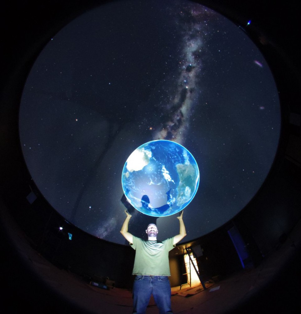 Travis Laurance, director of the Harry C. Vaughn University of Wyoming Planetarium, appears to hoist the Earth on his shoulders. Star shows for campus and the public return to the planetarium Friday, Dec. 5. Laser shows return Friday, Dec. 12. (UW Photo)