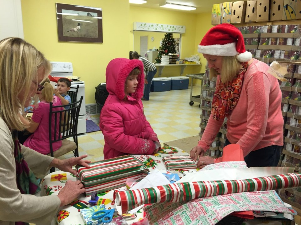 Makenna converses with Audrey Eaton and Melissa Strickler while they help wrap gifts for her grandmother.
