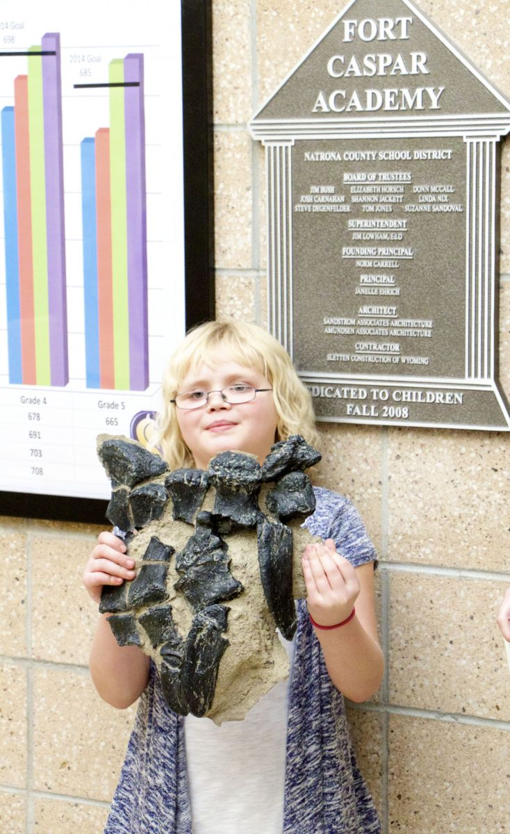 """4th grade student at Ft. Caspar Academy, Kaitlin Trost, holds her cast of the foot of """"Dopota the Dinosour!"""""""